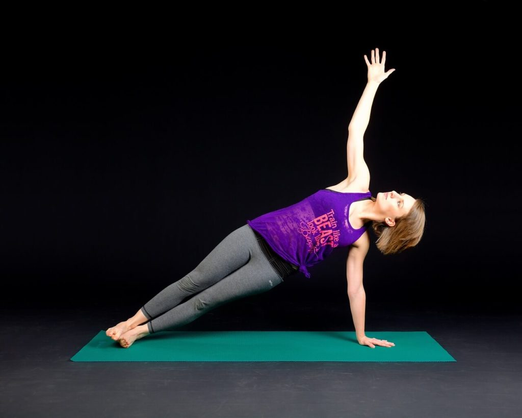 a woman is doing side plank